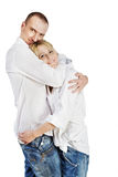 Man and woman stand hugging. Man and woman in white shirts and blue jeans stand hugging one each other Royalty Free Stock Image