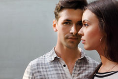 Man and woman stand near gray wall Stock Photography