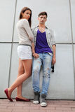 Man and woman stand near gray wall Stock Images