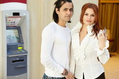 Man and woman stand near to cash dispenser. Dark-haired men and red-haired women stand near to cash dispenser, she holds credit card Stock Photography