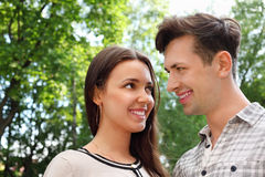 Man and woman stand in park and look at each other Royalty Free Stock Images