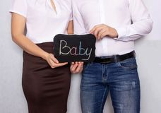 A man and a woman stand with a sign on which the baby is written, problems with the conception of children, male and royalty free stock photo