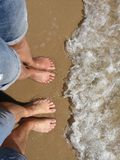 Man and woman stand with their feet on the beach. And let cold sea water flow over their feet Stock Photography