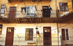 Man and woman stand thoughtfully on balconies on the different f Royalty Free Stock Image