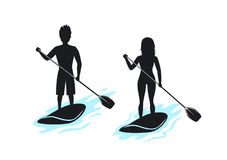 Man and woman stand up paddling. Paddleboarding silhouettes Royalty Free Stock Photos