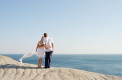 Man and woman standing arm in arm on a rock Stock Photo