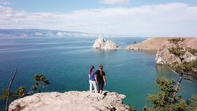 A man and a woman are standing on a cliff above the sea. Lake Baikal. Aerial shooting from the drone. Siberia, Russia stock video