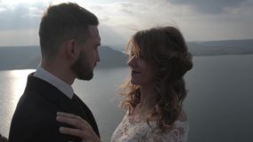 A man and a woman are standing on the edge of the cliff near the ocean, the hair is developing in the wind. White stock video