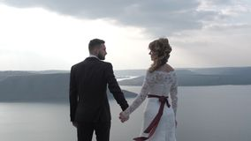A man and a woman are standing on the edge of the cliff near the ocean, the hair is developing in the wind. White stock footage