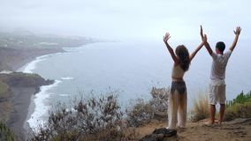 A man and a woman standing on the edge of a cliff overlooking the ocean raise their hands up and inhale the sea air stock footage