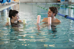 Man and woman standing with foam rollers in the pool Stock Image