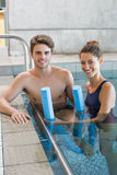 Man and woman standing with foam rollers in the pool Royalty Free Stock Photo