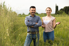 Man and woman standing in green field Royalty Free Stock Image