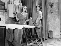Man and woman standing in a kitchen while she is ironing his pants and he is behind a curtain