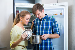 Man and woman standing near fridge Stock Images