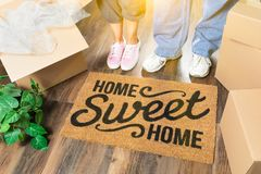 Man and Woman Standing Near Home Sweet Home Mat, Moving Boxes. Man and Woman Standing Near Home Sweet Home Welcome Mat, Moving Boxes and Plant Royalty Free Stock Photos
