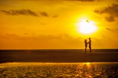 Man and Woman Standing Near Seashore Under Sunset Stock Photography