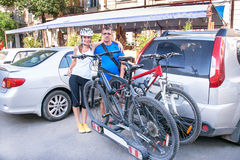 Man and woman are standing near two bicycles mounted on trunk of Royalty Free Stock Photo