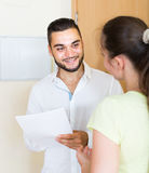 Man and woman standing with papers at the door Stock Images