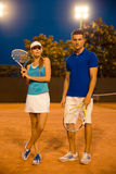 Man and woman standing with rackets at tennis court Stock Images