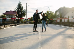 Man and woman standing at the railway crossing. Man and women standing at the railway crossing in the street Royalty Free Stock Photography
