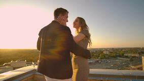 A man and a woman standing on the roof at sunset embrace and look at the beautiful view