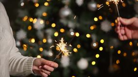 Two people are holding and waving bengal fires on New year party. Man and woman are standing in a room with Christmas tree and using sparklers on a party. Close stock footage