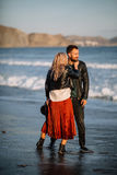 Man and woman standing on the sandy beach near the sea. Man and women standing on the sandy beach near the sea in an embrace Stock Photo