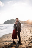 Man and woman standing on the sandy beach near the sea. Man and women standing on the sandy beach near the sea in an embrace Stock Images