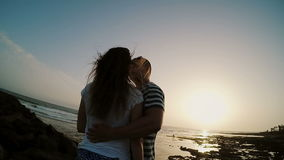 Man and woman standing on the shore by the sea, hugging and kissing on the sunset. Couple on sunset beach. Young man and woman standing on the shore by the sea stock video