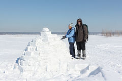 Man and woman standing to an igloo on a snow glade. Man and women standing to an igloo on a snow glade in the winter stock images