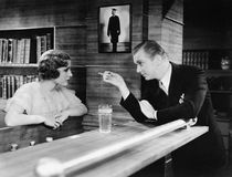 Man and woman standing together at a bar counter and talking Stock Photo