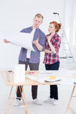 Man and woman standing together and consulting. Man and the women standing together close to the drafting board and consulting the project with the ladder behind Royalty Free Stock Photo