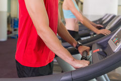 Man and woman standing on treadmills Royalty Free Stock Photography
