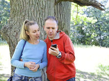 The man and the woman standing at a trunk of a huge tree, an oak show aside Royalty Free Stock Photography