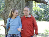 The man and the woman standing at a trunk of a huge tree, an oak show aside Royalty Free Stock Image