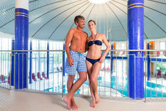 Man and woman standing in wellness thermal spa. Man and women standing in wellness thermal spa with columns and dome, the pool in the background Royalty Free Stock Photography