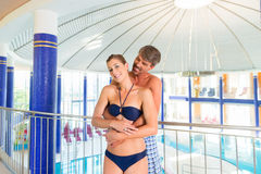 Man and woman standing in wellness thermal spa. Man and women standing in wellness thermal spa with columns and dome, the pool in the background Stock Image