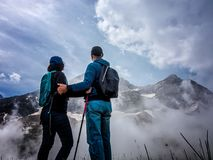 Man and woman stands on a hillside and admires the tops of mountains in the clouds stock image