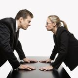 Man and woman staring. Caucasian mid-adult businessman and woman staring at each other with hostile expressions Stock Images