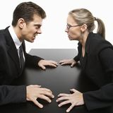 Man and woman staring at each other with hostile expressions. Caucasian mid-adult businessman and woman staring at each other with hostile expression Stock Photos