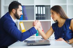 Man and woman staring at each other with hostile expressions. Man and women staring at each other with hostile expressions royalty free stock photography