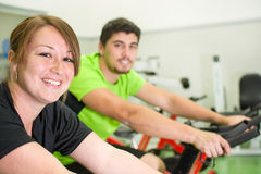 Man and woman with stationary bicycle in gym Royalty Free Stock Images