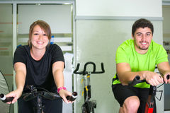 Man and woman with stationary bicycle in gym Royalty Free Stock Photos