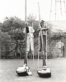 Man and woman on stilts holding giant golf clubs Stock Image