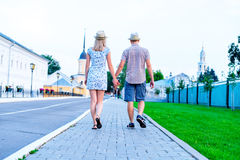 Man and woman are on stone pavement holding hands, summer in city, concept of event young family, newlyweds complex Royalty Free Stock Images