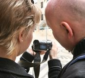 The man and the woman study the camera. The married couple has bought the new camera Royalty Free Stock Photo