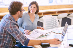 Man and woman study together to rech higher potential. Adult female tutor smiles politely at the male student that she is mentoring to help him reach his full royalty free stock images