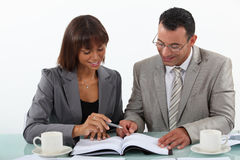 Man and woman studying. Man and women studying a book together Royalty Free Stock Images
