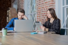 Man and woman successful content creators reading news on net-book and digital tablet. Two business person work together to create a new project in a social Royalty Free Stock Photo